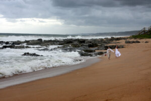 Bridal couple holding hands walking on the beach