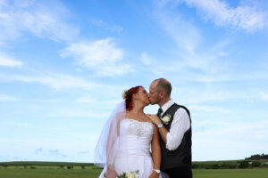 wedding couple kissing against a blue sky with white clouds