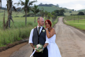 wedding couple posing next to a palm tree lined dirt road