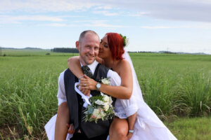 Groom piggybacking bride on his back next to a sugarcane field