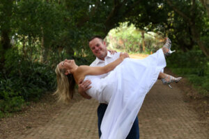 Groom picking up laughing bride in his arms