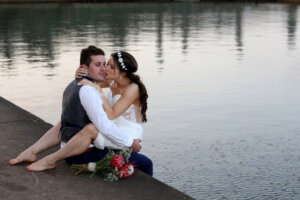 Bride sitting on grooms lap next to a pool while kissing him