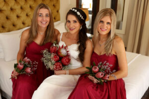 Bride with protea flower bouquet sitting on bed with two bridesmaids with red dresses