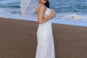 Beautiful bride posing with white umbrella on the beach