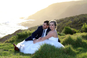 sitting bride and groom next to the ocean