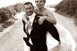 Groom in black tuxedo piggybacking bride