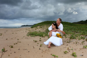 wedding couple posing on the beach with bride holding yellow sunflower bouquet