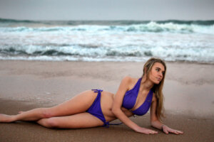 blond model with purple two piece bikini posing on the beach