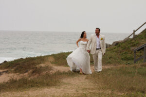 Bride and groom walking and holding hands with the ocean in the background
