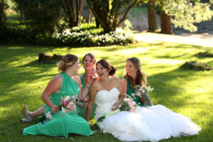 laughing bride and bridesmaids sitting on a green lawn