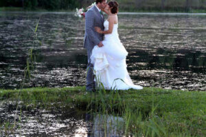 wedding couple kissing next to a lake in the late afternoon