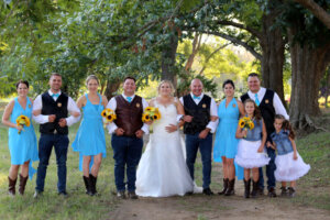 wedding party with bride and groom in the middle posing for wedding photographer