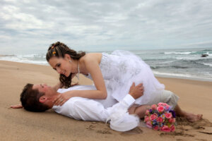 Wedding couple kissing on the beach while lying down