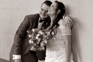 laughing bride with groom having one hand over her shoulder