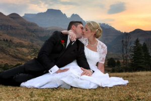 Bride and groom kissing with sunset and Drakensberg mountains in background