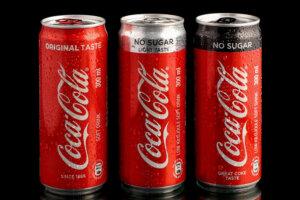 three Coca-Cola beverage cans