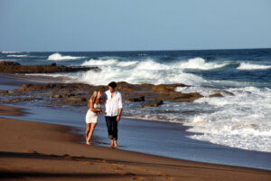 young couple walking and laughing on the beach