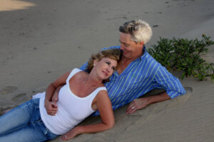 mature couple lying on the beach