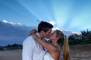 young couple kissing on the beach against setting sun backdrop