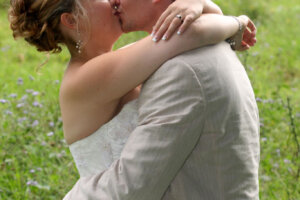 Wedding couple kissing with horses in background