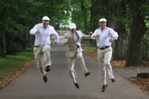 Three groomsmen jumping into the air in tree lined street