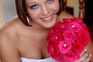Beautiful bride holding bouquet of red roses