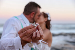 Wedding couple kissing while showing wedding rings