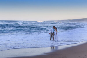 Wedding couple kissing while standing in shallow water on beach