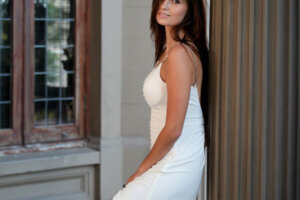 brunette model posing in white dress