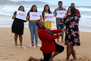 guy proposing to his wife on the beach with friends looking on