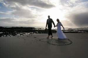 Silhouette of bridal couple walking on beach next to heart drawn in sand