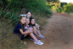 four young children sitting next to dirt road