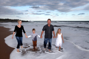 family of four mom dad and two kids walking along the beach holding hands