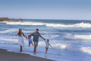 family of four walking along the beach