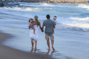 mom and dad each carrying a small child walking on the beach