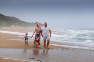 family of three mom dad and small boy walking on the beach