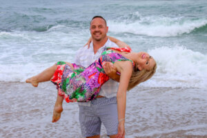 husband holding wife in his arms with ocean as background