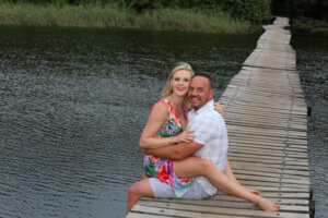 loving husband and wife couple sitting on the edge of a bridge