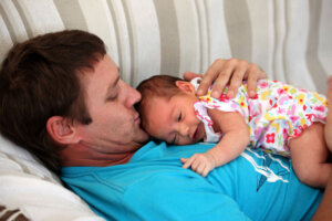 dad lying in bed with new born baby on his chest
