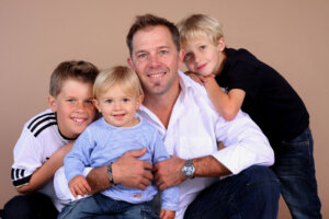photography studio portrait of dad and his three children