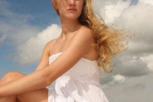 blond model in white sundress on the beach