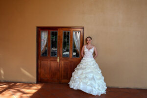 Beautiful bride posing for wedding photographer against wall