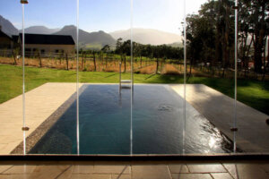 view of pool vineyard and mountains in background from inside luxury residential property