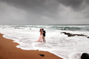 Bride and groom kissing on stormy beach