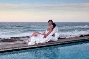 Bridal couple sitting next to swimming pool with ocean backdrop