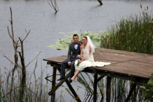 Bride and groom sitting on a wooden jetty