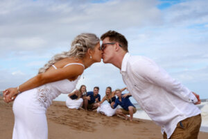 Bride and groom kissing on beach with bridal party looking on