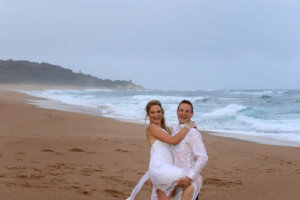 Bridal couple on beach with small airplane flying overhead