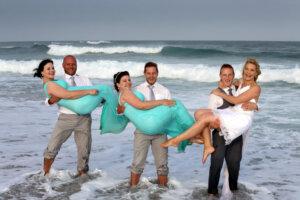groomsmen holding bridesmaids with ocean in background