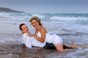bridal couple kissing in shallow oceanwater